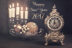 Vintage still life with alarm clock on Christmas Eve. Vintage alarm clock showing five to twelve and burning candles in candlestick in a study room. Text `Happy Royalty Free Stock Images