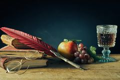 Vintage still life for college or an author. Vintage still life for college or a writer with a feather quill pen and reading glasses resting on old books royalty free stock images