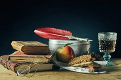 Vintage still life of evening studies for college. With a goblet of wine alongside old books, spectacles, a feather quill and tin container with sandwiches and stock images