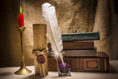 Vintage still life with glasses on old books near inkstand, feather, old paper and burning candle on canvas background Royalty Free Stock Photo
