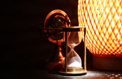 Vintage Still Life. Hourglass near old brass globe and glowing lamp on dark background Stock Photos