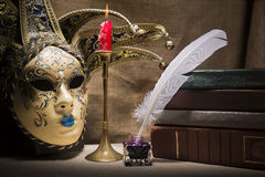 Vintage still life with old books near inkstand, feather, venezian mask and burning red candle in candlestick on canvas background.  Stock Image