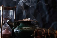 Vintage Still Life. Old hourglass and spectacles near extinguished candle with smoke royalty free stock image