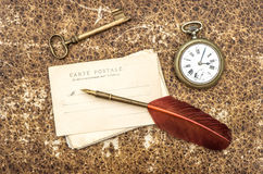 Vintage still life with old postcards, pocket watch, key and fea Royalty Free Stock Images