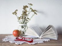 Vintage still life with an open book, glasses, apple and vase with flowers on doily. On the nightstand Stock Image