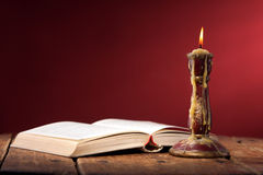 Vintage still life with open old book near candle Royalty Free Stock Photos