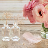 Vintage Still life with pink flowers in a vase with fearher and. Still life with pink flowers in a vase with fearher and two glass botles - vintage look Royalty Free Stock Photos