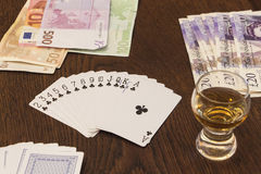 Vintage still life of playing cards, cash money and  shot of alc. Ohol. Concept of classical gambling games with cash money and alcohol Royalty Free Stock Images
