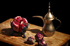 Vintage still life with pomegranate and teapot. Vintage still life with pomegranate, dried roses and arabic teapot on wooden table Stock Photos