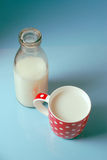 Vintage still life with red, in polka dot, cup of milk and antique bottle of milk on a blue background. Royalty Free Stock Image
