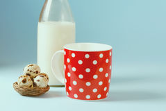 Vintage still life with red, in polka dot, cup of milk, quail eggs,  and vintage glass bottle Royalty Free Stock Images