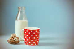 Vintage still life with red, in polka dot, cup of milk, quail eggs, and vintage glass bottle on a blue background. Royalty Free Stock Image