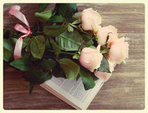 Vintage still life of roses and book on wood Stock Photos