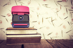 Vintage still life of stack of old books with old camera on swee Stock Image