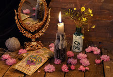 Vintage still life with the tarot cards, mirror, flowers and candle. Halloween concept, black magic or fortune telling rite with occult and esoteric symbols stock photography