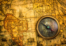 Vintage compass lies on an ancient world map Stock Image