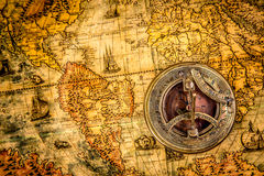 Vintage compass lies on an ancient world map Royalty Free Stock Image