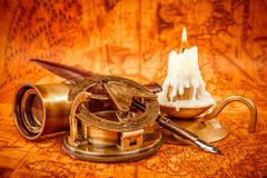 Vintage still life. Vintage items on ancient map. Vintage compass, magnifying glass, quill pen, spyglass lie on an old ancient map in 1565 with a lit candle royalty free stock photography