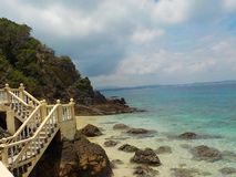 Vintage stone stairs on the edge of the rocks over the blue ocean, Malaysia royalty free stock image