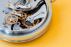 Vintage stopwatch chronometer closeup photo. Cogwheel gears wheels mechanic connection concept. Macro view, selective. Focus. Yellow paper background Stock Photos