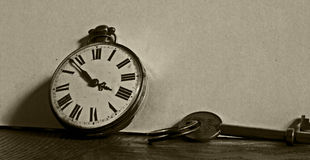 Vintage stopwatch and key. In a sepia tone stock photos