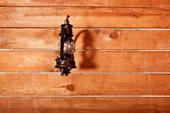 Vintage storm lantern hanging on wooden wall. Vintage storm lantern hanging on red wooden wall stock photography