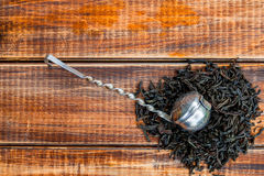 Vintage strainer with dry leaves of black tea on wooden background. Tea concept. Tea leaves. Top view. Closeup. Copy Royalty Free Stock Image