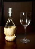 Vintage straw bottle of wine and glass wine.  Royalty Free Stock Image