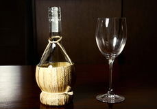 Vintage straw bottle of wine and glass wine.  Stock Photography