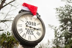 Vintage street clock with the inscription Happy New Year 2018 and Santa Claus hat on them. Outdoors in winter park Stock Photos