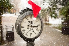 Vintage street clock with title Happy New Year 2018 and Santa Claus hat on them with falling snowflakes. Vintage street clock with the inscription Happy New Year Stock Photography