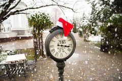 Vintage street clock with title Happy New Year 2018 and Santa Claus hat on them in snowy park. Vintage street clock with the inscription Happy New Year 2018 and Royalty Free Stock Images