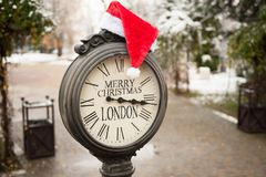 Vintage street clock with title Merry Christmas London and Santa Claus hat on them in winter park Stock Images