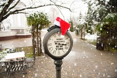 Vintage street clock with title Merry Christmas New York and Santa Claus hat on them with falling snowflakes. Vintage street clock with the inscription Merry stock photos