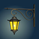 Vintage street hanging lamp, glowing with yellow light against the evening sky, with a cast-iron wall mount. With curls Royalty Free Stock Photography
