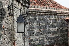 Vintage street iron lamp hanging on medieval wall Stock Image
