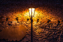 Vintage street lamp against a brick wall at night Stock Images