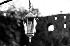 Vintage street lamp full of flies hanging on a chain. Black and white image stock photo