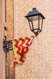 Vintage street lamp on the wall of a building in the Spanish. City of Tarragona. Spain flag on a city street lamp. The patterns on the wall Royalty Free Stock Photography
