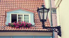 Vintage street lamp on wall and window in garret roof Royalty Free Stock Images