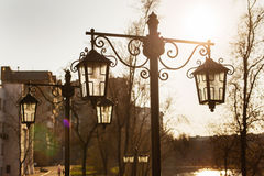 Vintage street lamps against backlight on sunset background Royalty Free Stock Image