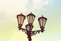 Vintage street light against blue sky. Royalty Free Stock Photo