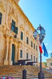 The streetlights in Castille Place, Valletta, Malta. The vintage streetlight with flags of Malta and EU at the staircase, rising to the main entrance of Auberge Stock Photos