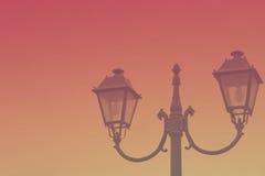 Vintage streetlight on sunset background. Toned image Stock Photography