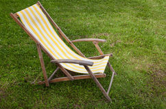 Vintage striped collapsible garden chair on the lawn. A vintage striped collapsible garden chair on the lawn Royalty Free Stock Image
