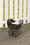 Vintage stroller in front of white fence Stock Photos