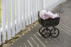 Vintage stroller in front of white fence Stock Photography
