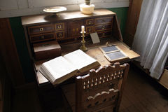 Vintage study interior. Vintage intimate scene with old desk, open bible and sunlight Royalty Free Stock Images