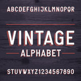 Vintage style alphabet vector font. Letters and numbers on the dark wooden background. Retro vector typeface for labels, flyers, headlines, posters etc Stock Images