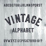 Vintage style alphabet vector font. Letters and numbers on the light wooden background. Stock Images